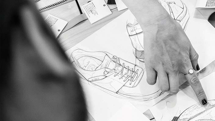 A hand pointing at a hand drawn shoe design